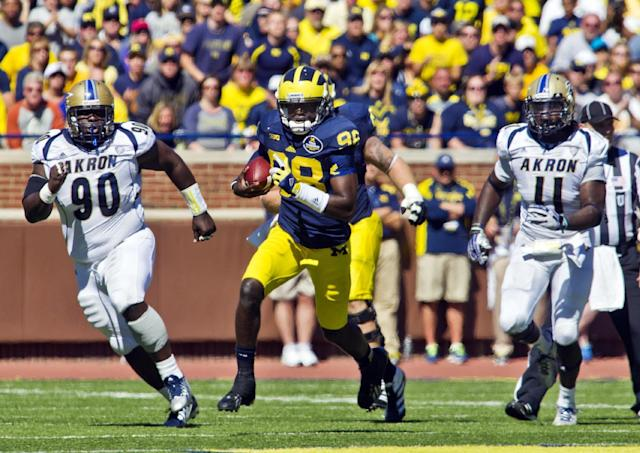 Michigan quarterback Devin Gardner (98), pursued by Akron defensive lineman Moses McCray (90) and safety Johnny Robinson (4), rushes for 35 yards in the fourth quarter of an NCAA college football game in Ann Arbor, Mich., Saturday, Sept. 14, 2013. Michigan won 28-24. (AP Photo/Tony Ding)
