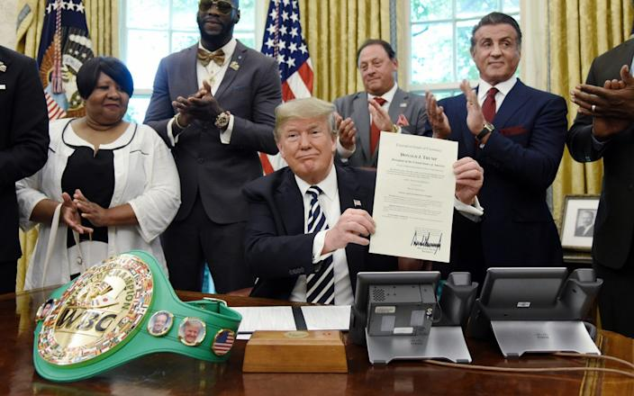 US President Donald Trump holds a signed Executive Grant of Clemency for boxer 'Jack Johnson' in the Oval Office - Pool/Getty Images North America