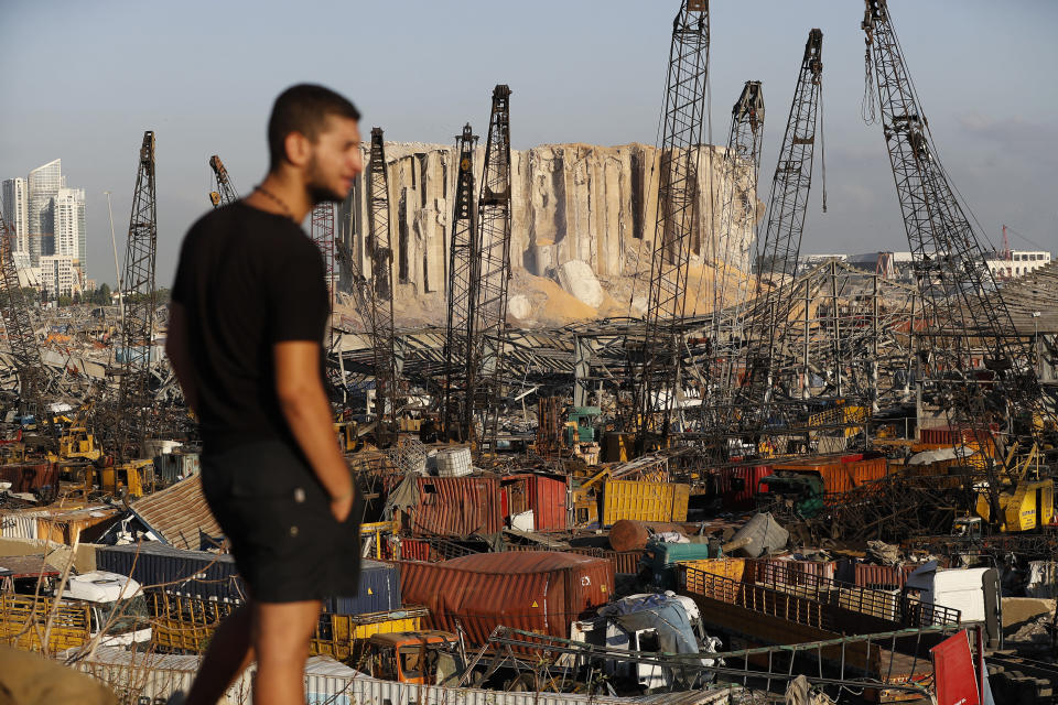 A man looks at the scene of Tuesday's explosion that hit the seaport of Beirut, Lebanon, Friday, Aug. 7, 2020. Rescue teams were still searching the rubble of Beirut's port for bodies on Friday, nearly three days after a massive explosion sent a wave of destruction through Lebanon's capital. (AP Photo/Hussein Malla)