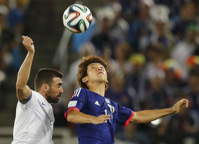 Greece's Giannis Maniatis fights for the ball with Japan's Yuya Osako (R) during their 2014 World Cup Group C soccer match at the Dunas arena in Natal June 19, 2014. REUTERS/Sergio Moraes (BRAZIL - Tags: SOCCER SPORT WORLD CUP TPX IMAGES OF THE DAY)
