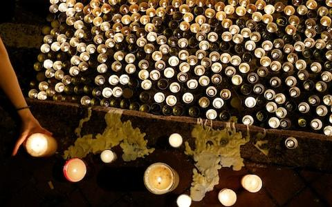 Protesters light candles in honour of a man who died after falling from a scaffolding at the Pacific Place complex while protesting - Credit: Reuters