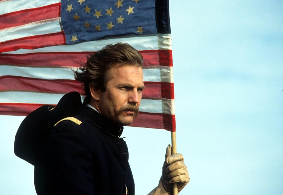 Kevin Costner holding an American flag in a scene from the film 'Dances With Wolves', 1990. (Photo by Tig Productions/Getty Images)