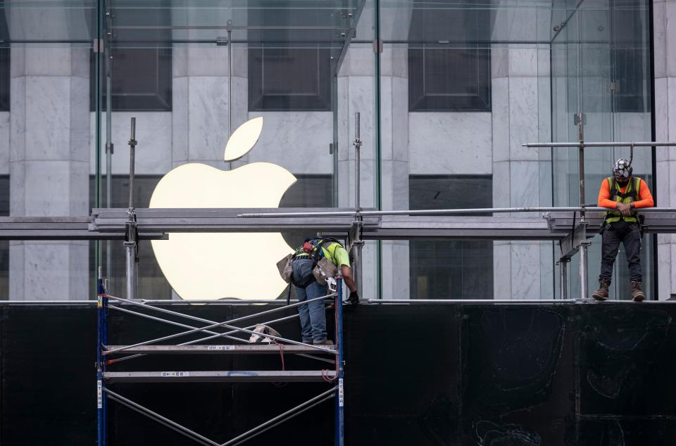 """Workers put up boards around the Apple flagship store on Fifth Avenue, after a night of protest over the death of an African-American man George Floyd in Minneapolis on June 2, 2020 in Manhattan in New York City. - New York's mayor Bill de Blasio yesterday declared a city curfew from 11:00 pm to 5:00 am, as sometimes violent anti-racism protests roil communities nationwide. Saying that """"we support peaceful protest,"""" De Blasio tweeted he had made the decision in consultation with the state's governor Andrew Cuomo, following the lead of many large US cities that instituted curfews in a bid to clamp down on violence and looting. (Photo by Johannes EISELE / AFP) (Photo by JOHANNES EISELE/AFP via Getty Images)"""