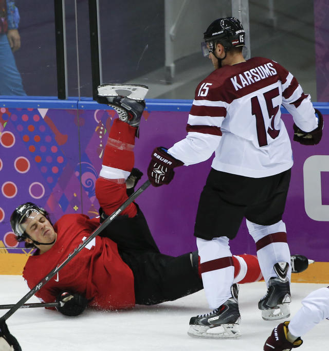 Switzerland forward Roman Wick falls to the ice as he is checked by Latvia forward Martins Karsums in the second period of a men's ice hockey game at the 2014 Winter Olympics, Tuesday, Feb. 18, 2014, in Sochi, Russia. (AP Photo/Julio Cortez)