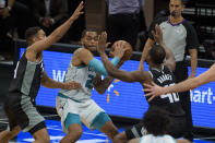 Charlotte Hornets forward P.J. Washington (25) is defended by Sacramento Kings guard Cory Joseph, left, and Sacramento Kings forward Harrison Barnes (40) during the second half of an NBA basketball game in Sacramento, Calif., Sunday, Feb. 28, 2021. The Hornets won 127-126. (AP Photo/Randall Benton)