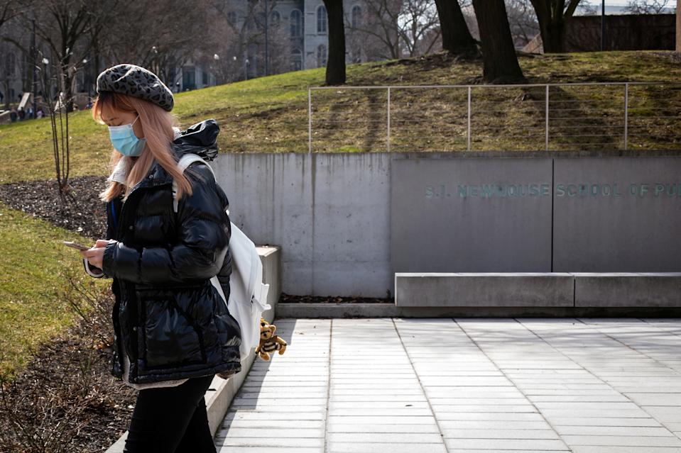 A woman wears a protective face mask as students prepare for Spring Break and an extended period of online classes due to coronavirus at Syracuse University, New York, U.S., March 12, 2020. Picture taken March 12, 2020. REUTERS/Maranie Staab
