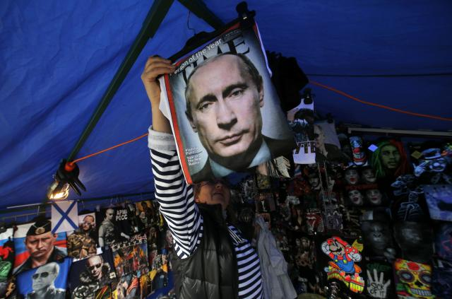 A vendor sells T-shirts printed with images of Russia's President Vladimir Putin at a street store in the center of St. Petersburg, August 31, 2014. Russia's President Vladimir Putin said on Sunday that Moscow could not stand aside when people were being shot at in Ukraine, he told Russia's state TV Channel 1 in an interview. REUTERS/Alexander Demianchuk (RUSSIA - Tags: SOCIETY POLITICS TPX IMAGES OF THE DAY)
