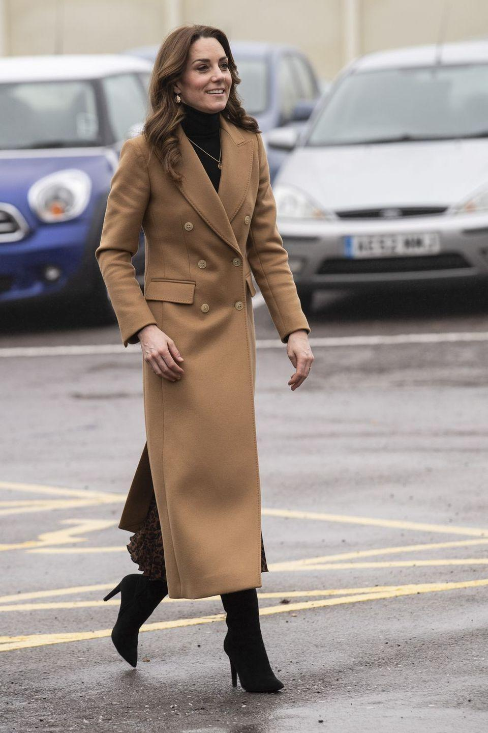 """<p>The Duchess of Cambridge visits HMP Send. She wore a black turtleneck and camel Chesterfield coat by <a href=""""https://www.massimodutti.com/us/"""" rel=""""nofollow noopener"""" target=""""_blank"""" data-ylk=""""slk:Massimo Dutti"""" class=""""link rapid-noclick-resp"""">Massimo Dutti</a> with a pleated leopard-print skirt by Zara. </p>"""