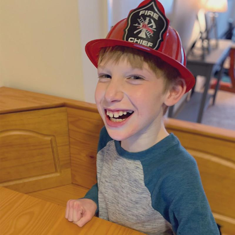 Firefighter used sign language to communicate with non verbal boy Tegan who is pictured enjoying his hat from the Manchester Fire Department.