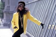 <p>A model in an oversized yellow blazer, complete with shoulder pads and a large chain necklace. </p>