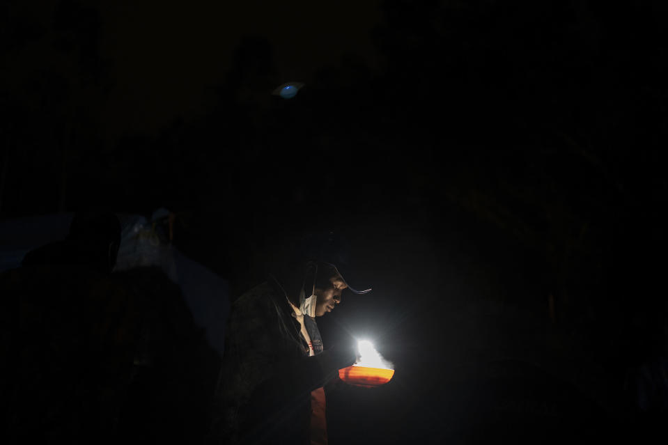 A migrant from Senegal has dinner in Las Raices camp in San Cristobal de la Laguna, in the Canary Island of Tenerife, Spain, Wednesday, March 17, 2021. Several thousand migrants have arrived on the Spanish archipelago in the first months of 2021. Due to the terrible living conditions and the poor quality of food and water at the Las Raices camp, some migrants have decided to leave the camp and sleep in shacks in a nearby forest instead. (AP Photo/Joan Mateu)