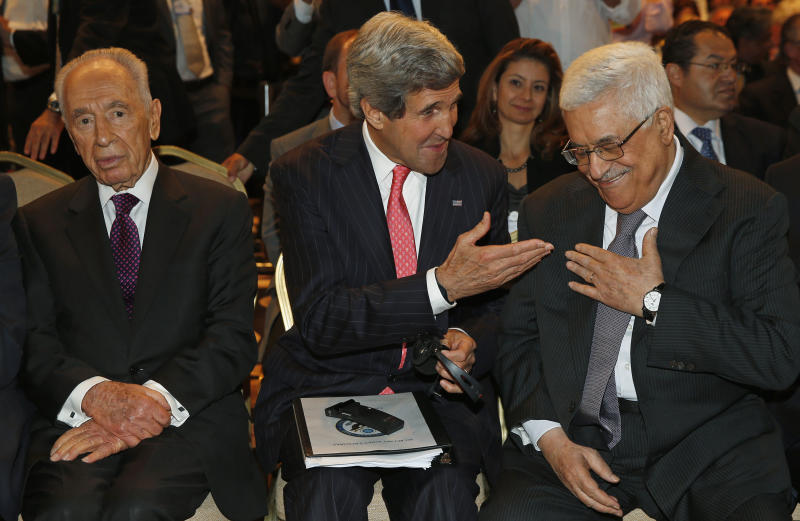 US Secretary of State John Kerry speaks with Palestinian President Mahmoud Abbas, right, as he sits next to Israeli president Shimon Peres at the World Economic Forum on the Middle East and North Africa at the King Hussein Convention Centre, at the Dead Sea May 26, 2013.  (AP Photo/Jim Young, Pool)
