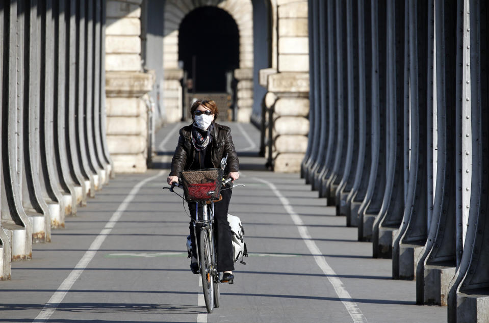 PARIS, FRANCE - APRIL 24: A woman wearing a protective face mask rides her bicycle under the Bir Hakeim bridge as the lockdown continues due to the coronavirus outbreak (COVID 19) on April 24, 2020 in Paris, France. The Coronavirus (COVID-19) pandemic has spread to many countries across the world, claiming over 191,000 lives and infecting over 2.7 million people. (Photo by Chesnot/Getty Images)