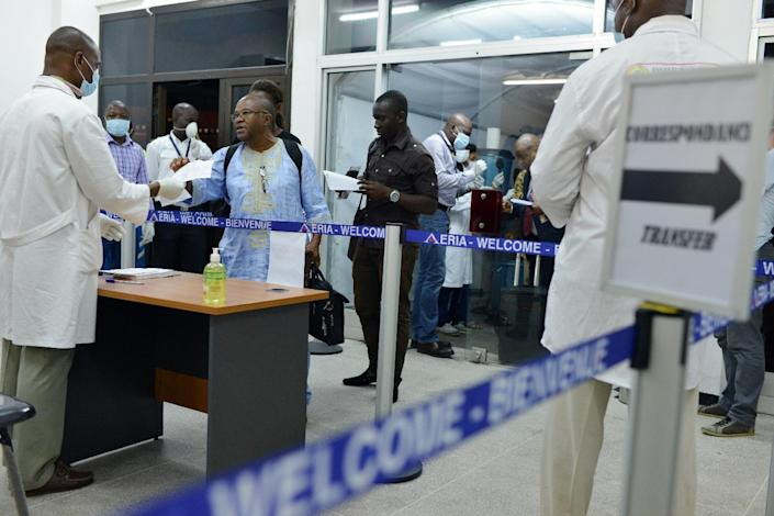 Medical staff, wearing protective masks, check health forms belonging to passengers arriving from Conakry in Guinea at the airport in Abidjan on October 20, 2014 (AFP Photo/Issouf Sanogo)