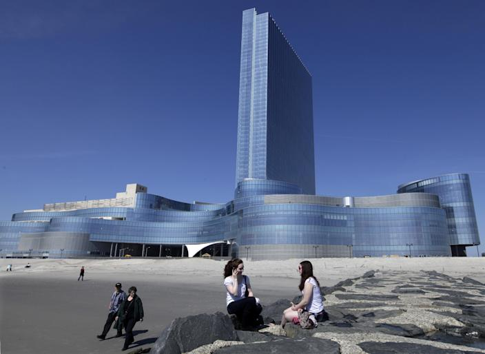 FILE - In this March 19, 2012 file photo, Kati MacFarline, left, of Nashua, N.H., and Christine Kashian, of Caribou, Maine, sit on a jetty near Revel in Atlantic City, N.J. Revel, the casino many people had hoped would turn around Atlantic City's sagging fortunes, said Tuesday, Feb. 19, 2013 that it will file for Chapter 11 bankruptcy protection in March, less than a year after it opened. (AP Photo/Mel Evans, File)