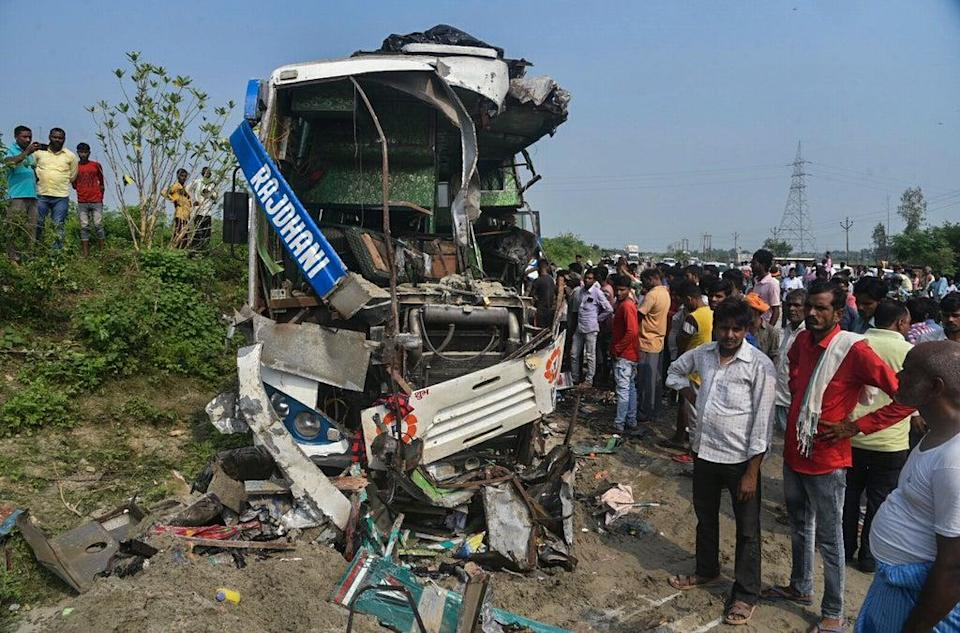 People stand near the wreckage of a bus that collided with a truck in Barabanki district in Uttar Pradesh state, India (AP)