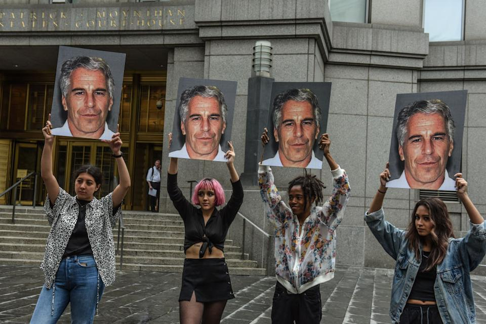 """A protest group called """"Hot Mess"""" hold up signs of Jeffrey Epstein in front of the Federal courthouse on July 8, 2019 in New York City. Source: Stephanie Keith/Getty Images"""