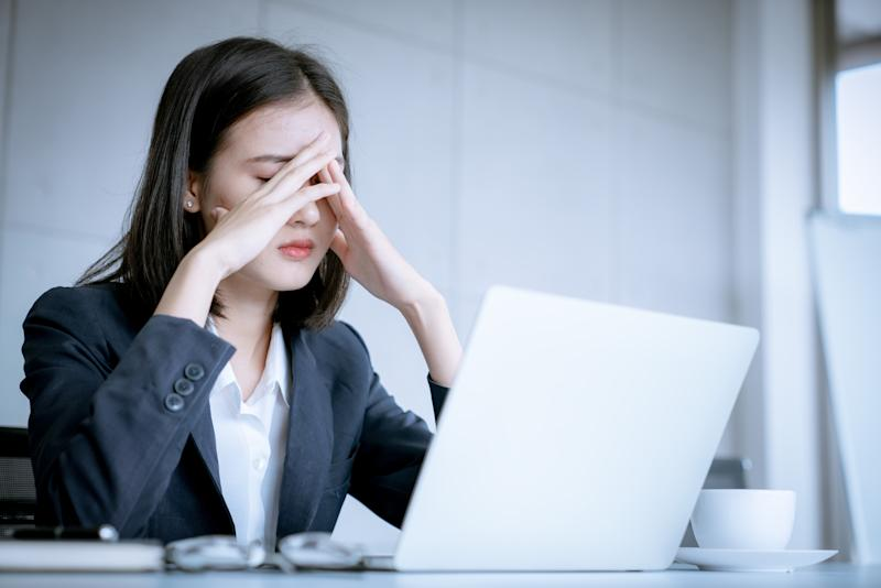 A woman in professional dress sits in front of a laptop, her hands covering her face in apparent exasperation.