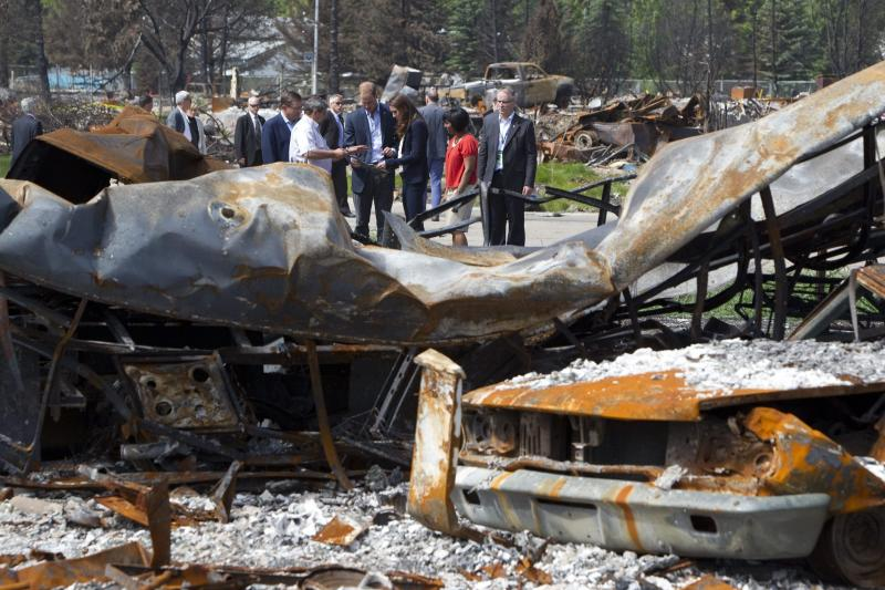 Prince William and his wife, Kate, the Duke and Duchess of Cambridge tour a fire-damaged area of  Slave Lake, Alberta, Canada  on Wednesday, July 6, 2011. More than 400 homes and businesses, about one-third of the town , were reduced to ash and debris when a wind-whipped forest fire swept through in May. (AP Photo/The Canadian Press, Jonathan Hayward)