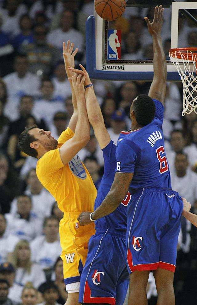 Golden State Warriors center Andrew Bogut (12) has his shot blocked by Los Angeles Clippers center DeAndre Jordan (6) during the first half of an NBA basketball game, Wednesday, Dec. 25, 2013, in Oakland, Calif. (AP Photo/Tony Avelar)