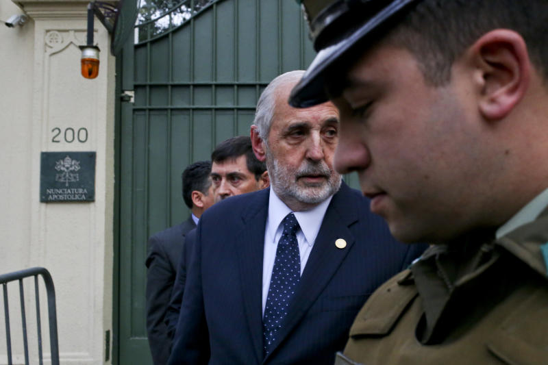 Chile's General Attorney Jorge Abbott, center, leaves the Apostolic Nunciature after meeting with Archbishop Charles Scicluna in Santiago, Chile, Wednesday, June 13, 2018. Police and prosecutors raided Roman Catholic Church offices in two Chilean cities Wednesday looking for files, investigative reports and documents related to a sex abuse scandal that has damaged the clergy's reputation in the South American country. (AP Photo/Esteban Felix)
