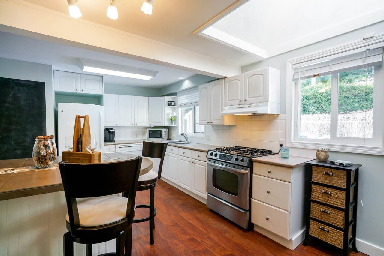 """<p><a rel=""""nofollow"""" href=""""https://www.zoocasa.com/surrey-bc-real-estate/5208111-8840-harvie-road-surrey-bc-v4n4b8-r2254565"""">8840 Harvie Rd., Surrey, B.C.</a><br /> The warm kitchen has bright white cabinets, and includes the fridge, stove and dishwasher.<br /> (Photo: Zoocasa) </p>"""