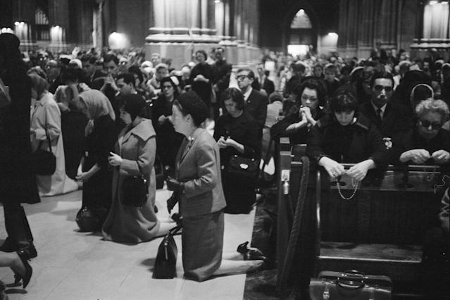 <p>Mourners pray on their knees in the pews and aisles of St. Patrick's Cathedral in New York City after the assassination of President John F. Kennedy in Dallas, Texas on Nov. 22, 1963. (Photo: Bettmann/Getty Images) </p>