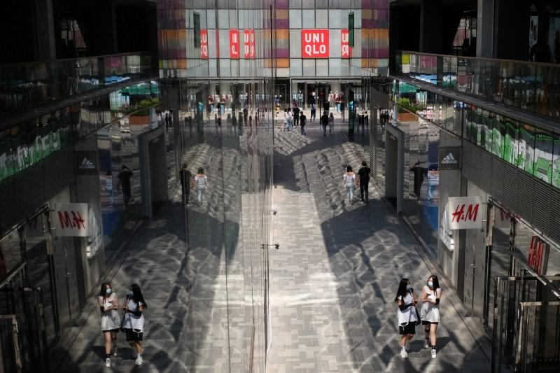 People walk past H&M and the Fast Retailing's Uniqlo stores at a shopping complex in Beijing