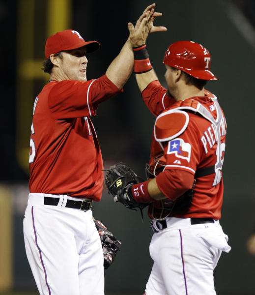 Texas Rangers closer Joe Nathan, left, high-fives catcher A.J. Pierzynski (12) after the final out of a baseball game against the Tampa Bay Rays, Monday, April 8, 2013, in Arlington, Texas. The Rangers won 5-4. (AP Photo/LM Otero)