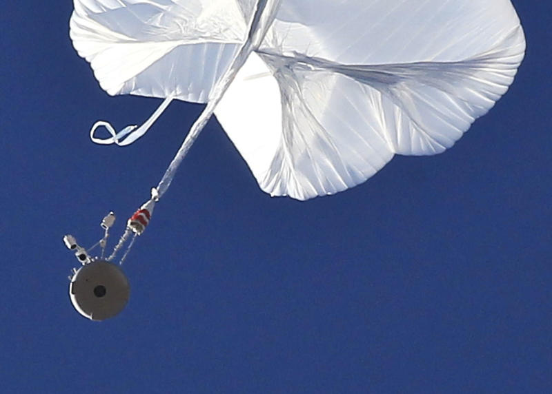 The capsule, bottom left, and attached helium balloon carrying Felix Baumgartner lifts off as he attempts to break the speed of sound with his own body by jumping from a space capsule lifted by a helium balloon, Sunday, Oct. 14, 2012, in Roswell, N.M. Baumgartner plans to jump from an altitude of 120,000 feet, an altitude chosen to enable him to achieve Mach 1 in free fall, which would deliver scientific data to the aerospace community about human survival from high altitudes.(AP Photo/Ross D. Franklin)