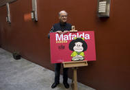 """FILE - In this Nov. 26, 2008 file photo, Argentine cartoonist Joaquin Salvador Lavado, better known as """"Quino,"""" poses with his character Mafalda during a news conference in Mexico City. Lavado passed away on Wednesday, Sept. 30, 2020, according to his editor Daniel Divinsky who announced it on social media. (AP Photo/Dario Lopez-Mills, File)"""