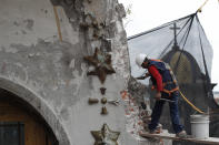 A worker seals a crack with a traditional mortar to keep loose pieces from falling from the damaged cupola, in the early stages of reconstruction work at Nuestra Senora de Los Angeles, or Our Lady of Angels church, three years after an earthquake cracked walls and collapsed nearly half of the 18th-century dome in Mexico City, Friday, Oct. 16, 2020. The $2 million restoration effort here will take at least two years more. (AP Photo/Rebecca Blackwell)