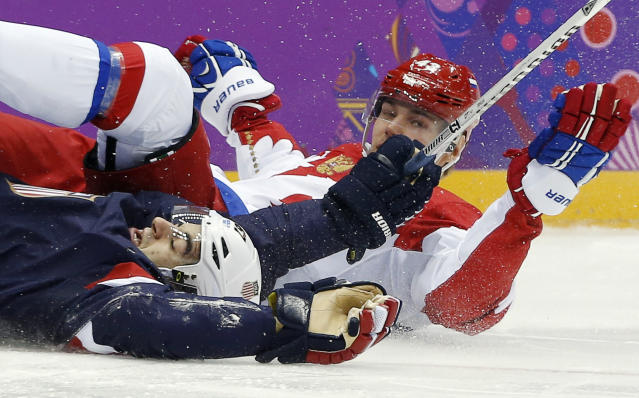 USA forward Max Pacioretty and Russia forward Valeri Nichushkin hit the ice in the second period of a men's ice hockey game at the 2014 Winter Olympics, Saturday, Feb. 15, 2014, in Sochi, Russia. (AP Photo/Julio Cortez)