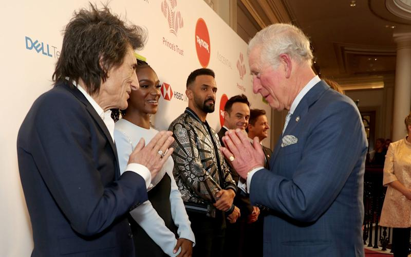 Prince Charles, Prince of Wales uses a Namaste gesture to greet Rolling Stone Ronnie Wood as he attends the Prince's Trust And TK Maxx & Homesense Awards at London Palladium on March 11, 2020 in London, England -Debrett's set to update etiquette guidelines to include no handshakes and shorter picnics - GETTY IMAGES