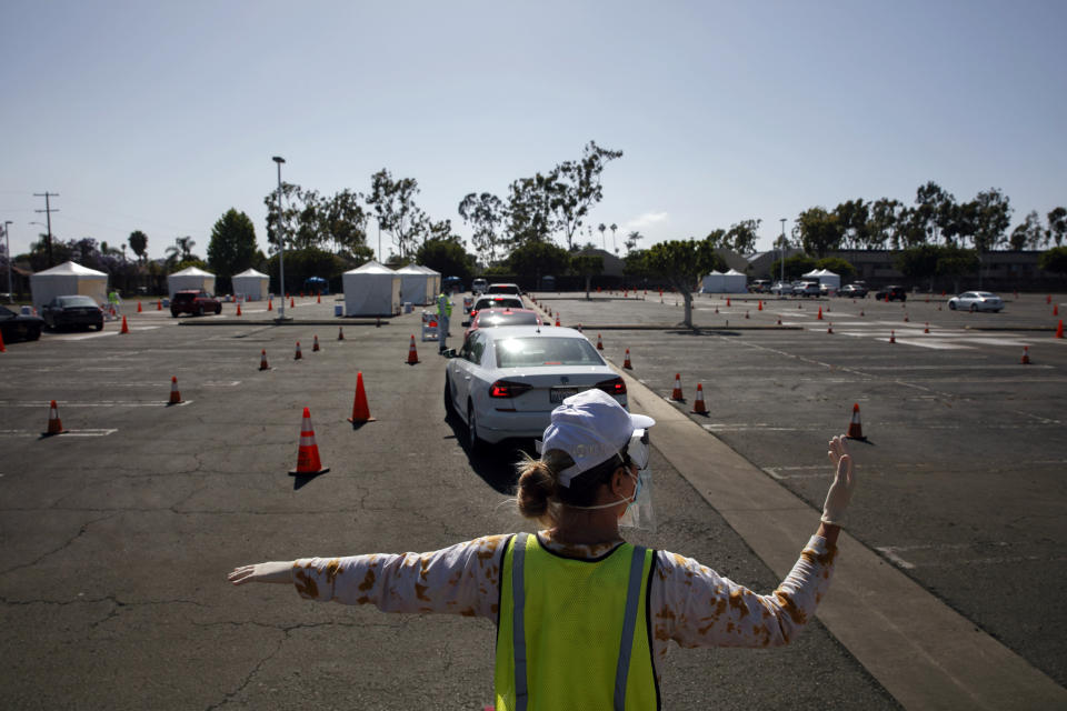 A volunteer controls traffic at a city-run, drive-thru COVID-19 testing site in South Central Los Angeles, Friday, May 22, 2020. While most of California is welcoming a slight return toward normal this holiday weekend, Los Angeles will not be joining the party. The nation's largest county is not planning to reopen more widely until the next summer holiday, July 4th, because of a disproportionately large share of the state's coronavirus cases and deaths that have hampered the county's ability to rebound and meet strict criteria to get more people back to work. (AP Photo/Jae C. Hong)