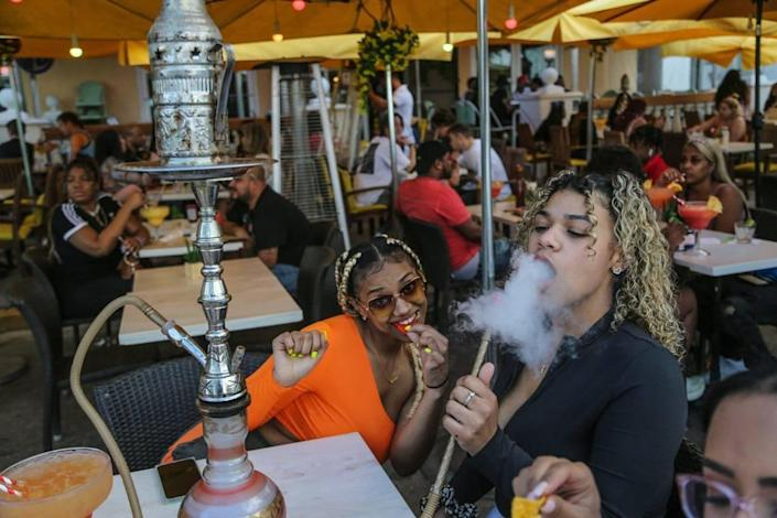 On Thursday, March 12, 2021, spring breakers Karsyn Mcleod, 21, and Zayasha Fowler, 21, sit in a water gisel bar and lounge on Ocean Drive, South Beach.