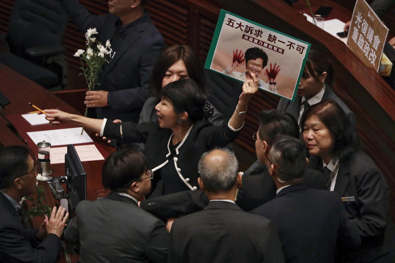 Security officials approach as pro-democracy lawmaker Claudia Mo, center, shouts while Hong Kong Chief Executive Carrie Lam attends a question and answer session in Hong Kong, Thursday, Oct. 17, 2019. (AP Photo/Mark Schiefelbein)