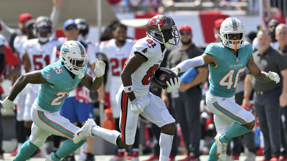 Tampa Bay Buccaneers wide receiver Antonio Brown (81) beats Miami Dolphins cornerback Xavien Howard (25) and free safety Nik Needham (40) on a 62-yard touchdown reception from quarterback Tom Brady during the first half of an NFL football game Sunday, Oct. 10, 2021, in Tampa, Fla. (AP Photo/Jason Behnken)