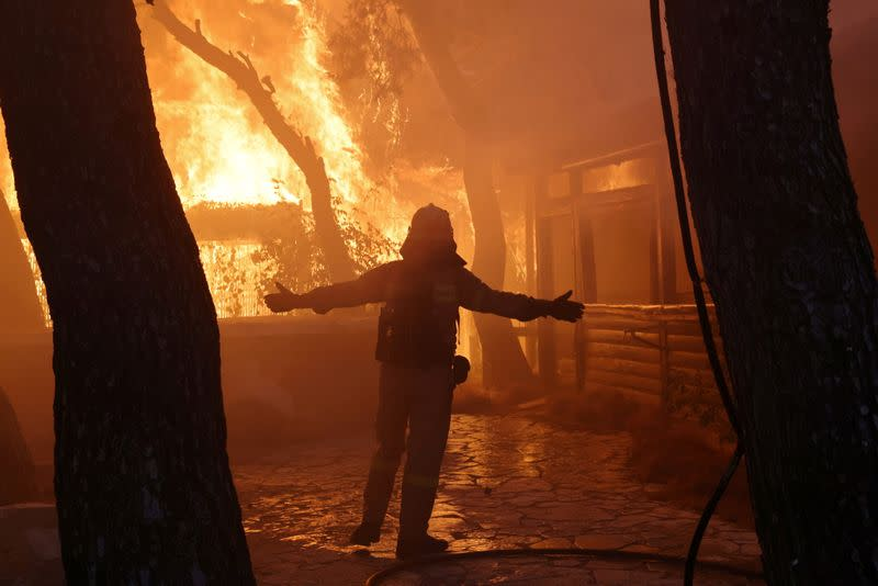 FILE PHOTO: A firefighter reacts as a wildfire burns at Varympompi suburb north of Athens, Greece, August 3, 2021
