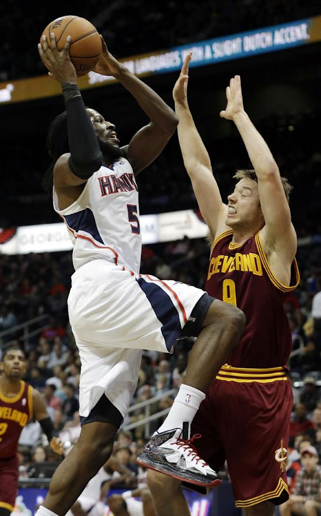 Atlanta Hawks small forward DeMarre Carroll (5) goes to the basket as Cleveland Cavaliers shooting guard Matthew Dellavedova defends in the first half of an NBA basketball game Friday, Dec. 6, 2013, in Atlanta. (AP Photo/John Bazemore)