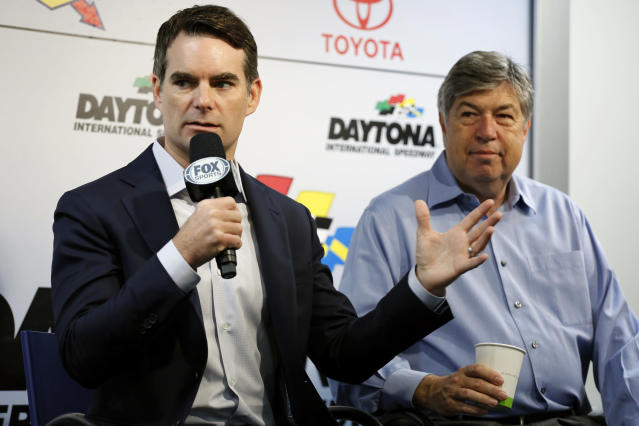 FILE - In this Feb. 18, 2016, file photo, NASCAR Cup Series champion Jeff Gordon, left, speaks to the media as announcer Mike Joy, right, listens during a news conference before practice for the Daytona 500 Sprint series auto race at Daytona International Speedway in Daytona Beach, Fla. NASCAR will have a much different feel when it resumes this weekend as the two-man broadcast team for Fox will not travel to Darlington Raceway and instead call the race from a studio in Charlotte. (AP Photo/Terry Renna, File)