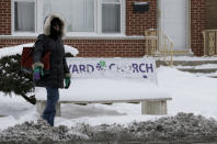 A woman waits for a bus at a bus stop in Chicago, Friday, Jan. 3, 2014. The snowstorm may finally have left town but a winter weather advisory is in effect for this evening when southerly winds are expected to kick up blizzard-like conditions. (AP Photo/Nam Y. Huh)