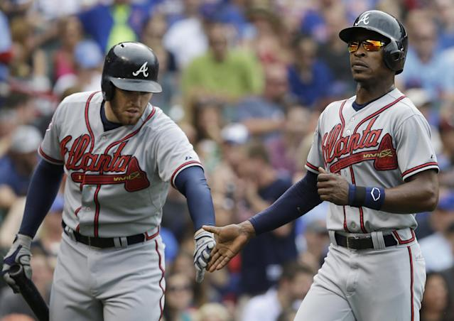 Atlanta Braves' B.J. Upton, right, celebrates with Freddie Freeman after scoring on a single hit by Andrelton Simmons during the third inning of a baseball game against the Chicago Cubs in Chicago, Saturday, July 12, 2014. (AP Photo/Nam Y. Huh)
