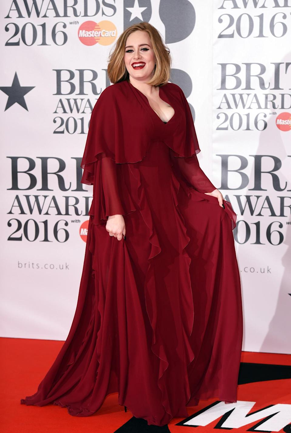 <p>The musician looked simply stunning in a ruffled oxblood gown. <i>[Photo: Rex]</i></p>