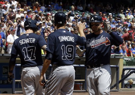 Atlanta Braves' Brian McCann, right, is congratulated by teammates Jordan Schafer (17) and Andrelton Simmons (19) afterhitting a grand slam during the first inning of a baseball game against the Milwaukee Brewers, Sunday, June 23, 2013, in Milwaukee. (AP Photo/Morry Gash)