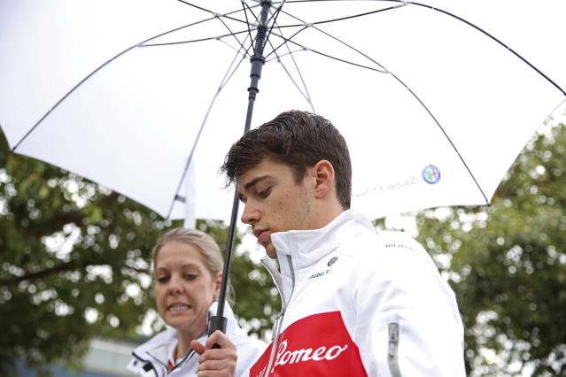 Sauber driver Charles Leclerc, right, of Monaco is kept dry with an umbrella as he arrives at the Australian Formula One Grand Prix in Melbourne, Saturday, March 24, 2018. The first race of the 2018 seasons is on Sunday. (AP Photo/Asanka Brendon Ratnayake)