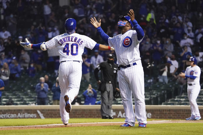 Chicago Cubs' Willson Contreras, left, and third base coach Willie Wilson, right, gesture as he runs the bases after hitting a two-run home run against the Milwaukee Brewers during the fourth inning of a baseball game, Monday, April 5, 2021, in Chicago. (AP Photo/David Banks)