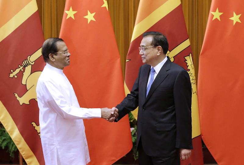 Sri Lankan President Maithripala Sirisena shakes hands with Chinese Premier Li Keqiang at the Great Hall of the People in Beijing on May 15, 2019