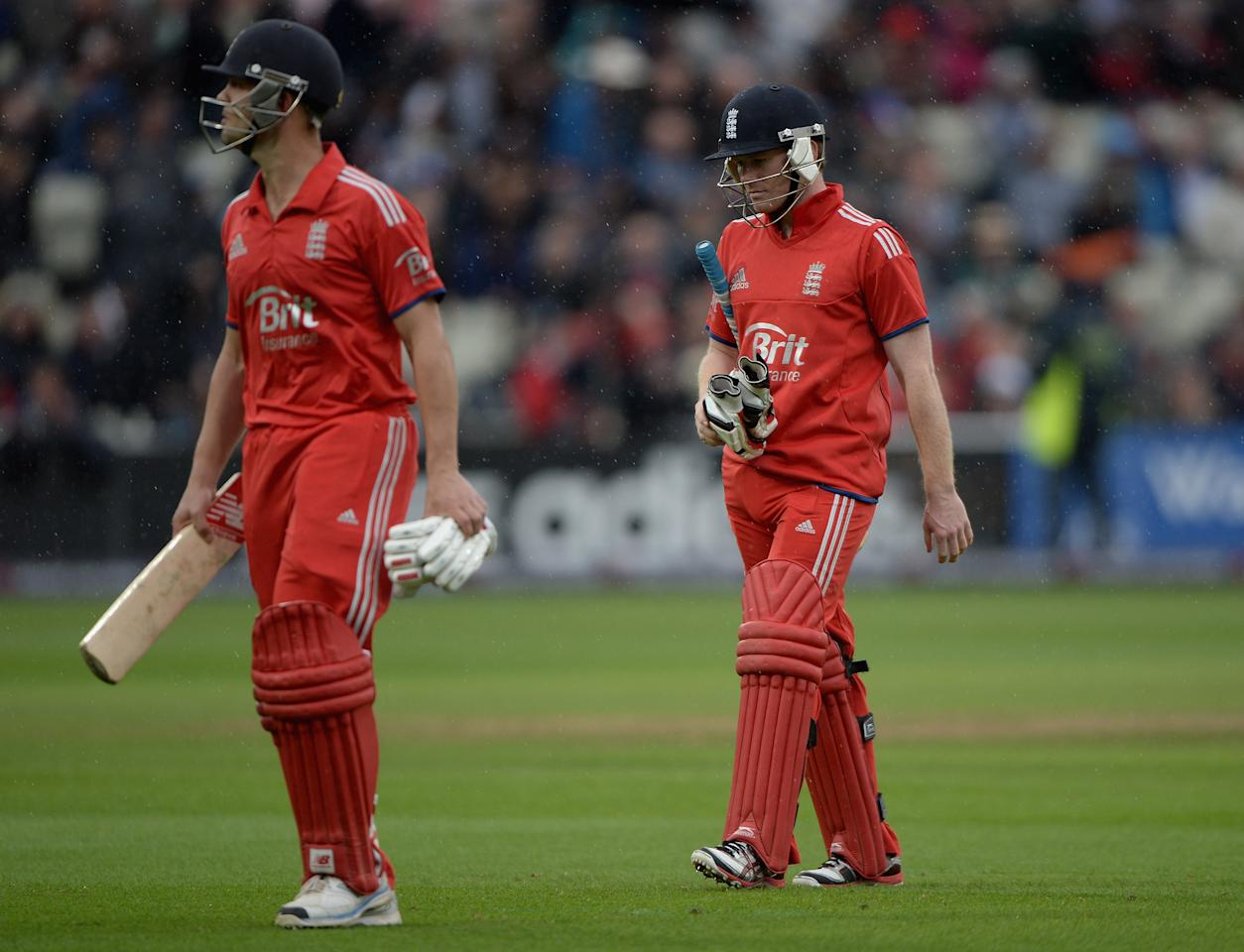 BIRMINGHAM, ENGLAND - SEPTEMBER 11:  England captain Eoin Morgan and Jonathan Trott leaves the field as rain stops play during the 3rd NatWest Series ODI match between England and Australia at Edgbaston on September 11, 2013 in Birmingham, England.  (Photo by Gareth Copley/Getty Images)