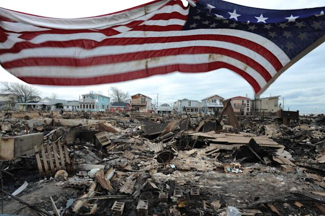 An American flag flies above a burned-out Breezy Point, Queens, in the aftermath of Hurricane Sandy. (Photo: David Handschuh/NY Daily News via Getty Images)
